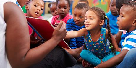 Teacher Helping Children Learn to Read